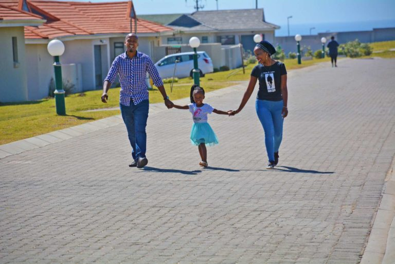Happy Family Walking Through The Village Kidds Beach Green Estate